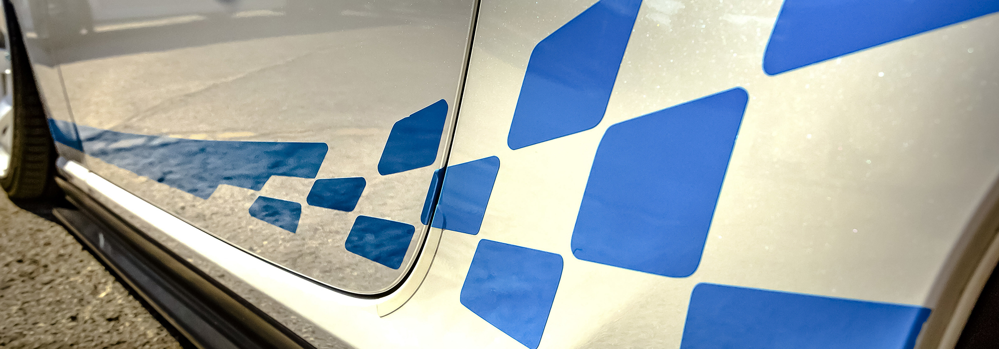 Blue decal on the exterior body of a white car