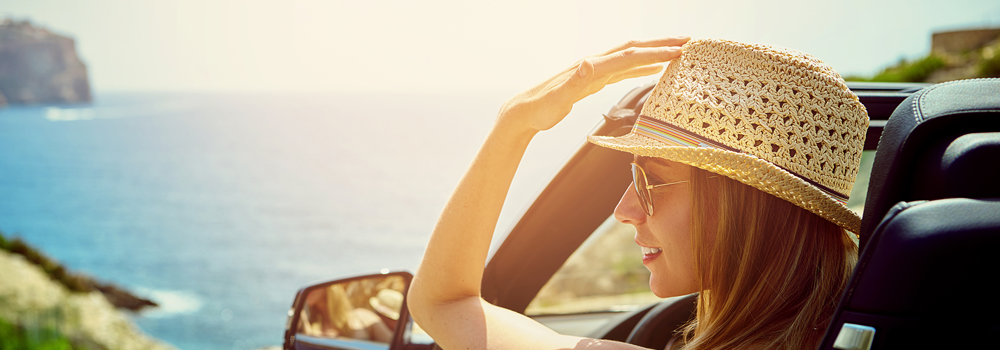 Side view on smiling woman in convertible car